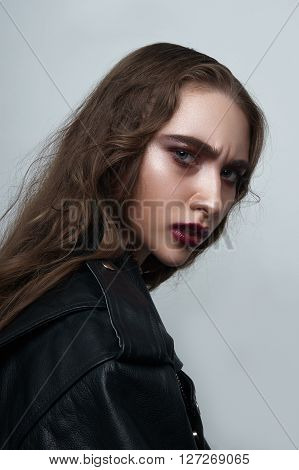 Agressive biker Girl with dark red Lips and black leather Jacket
