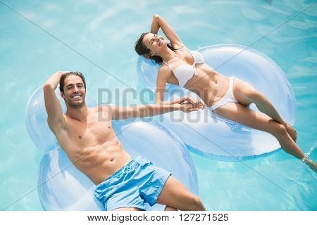 Young couple smiling while relaxing on inflatable ring at swimming pool
