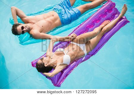High angle view of happy couple relaxing on inflatable raft at swimming pool