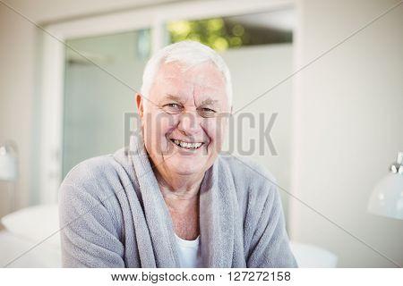 Portrait of happy senior man in bedroom at home
