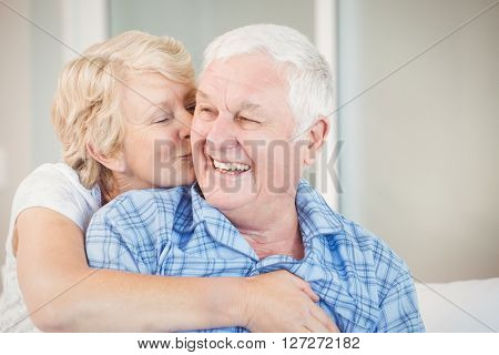 Happy senior woman kissing husband at home