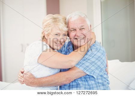 Happy senior couple looking away while embracing in bedroom at home