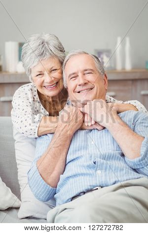 Smiling senior couple hugging while sitting on sofa at home
