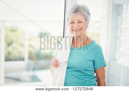 Portrait of smiling senior woman with towel at home