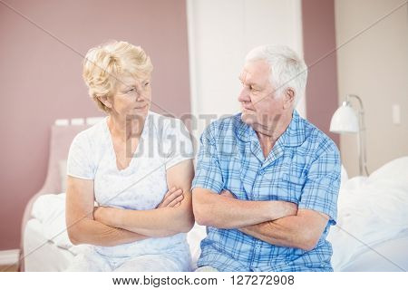 Serious couple with arms crossed sitting on bed at home