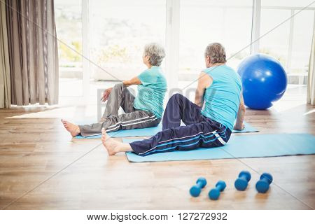 Rear view of couple doing yoga on exercise mat at home