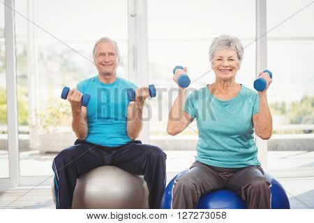 Portrait of smiling senior couple holding dumbbells while sitting on exercise ball at home