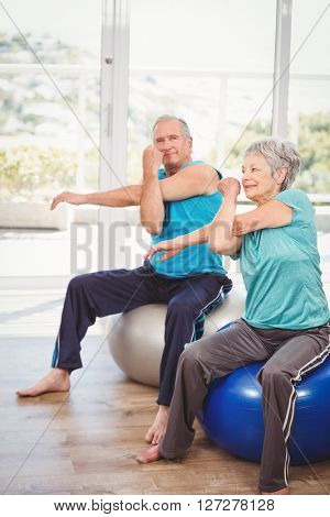 Portrait of senior man exercising with wife while sitting on exercise ball at home
