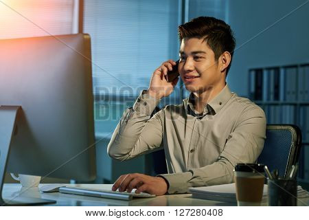 Smiling  young Filipino businessman talking on phone in dark office