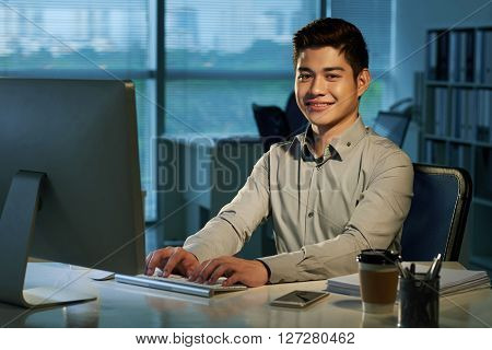 Portrait of cheerful Filipino businessman  at his workplace