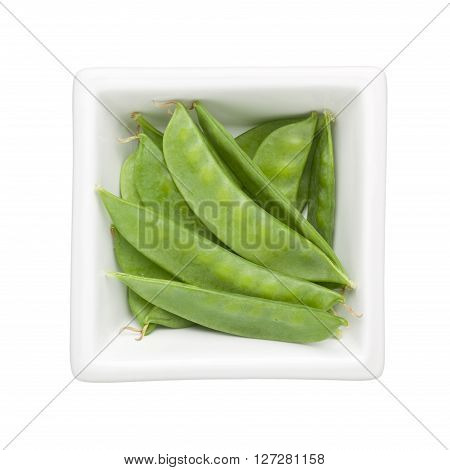 Snow peas in a square bowl isolated on white background