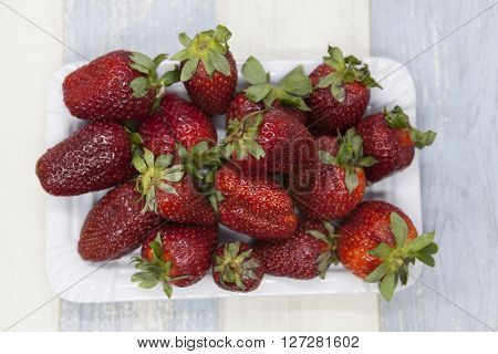 Fresh strawberry on a plate on a blue gray background.