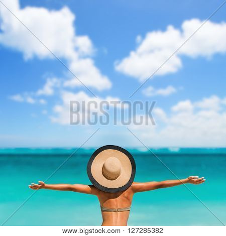 Summer vacation happiness carefree joyful sun hat woman with open arms in success enjoying tropical beach destination. Holiday bikini girl relaxing from behind on Caribbean vacation. Sky copyspace.