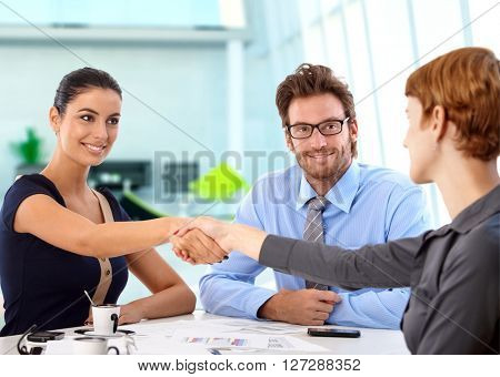 Young, attractive caucasian business people shaking hands on a successful deal at office meeting. Sitting at table, smiling.