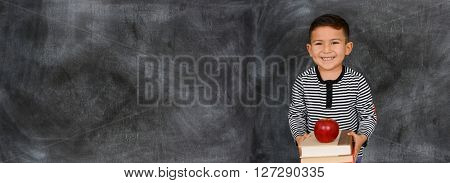 Young child who is standing with a chalkboard