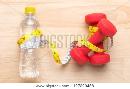 Fitness equipment. Healthy food. Apple, dumbbells and measuring tape on wooden background. View from above