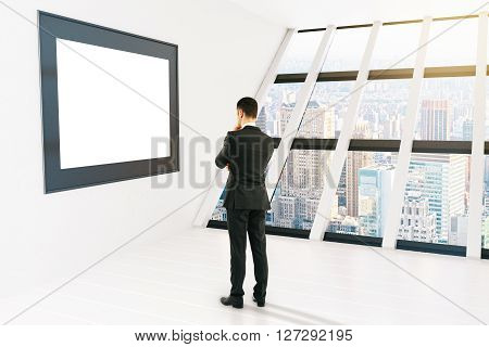 Thoughtful businessman looking at blank picture frame in white room with windows and city view. Mock up 3D Rendering