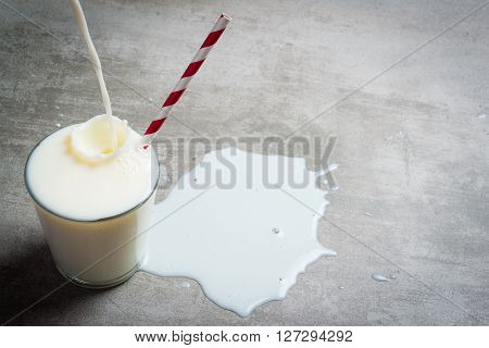 Milk Pouring Into Glass On A Concrete Table