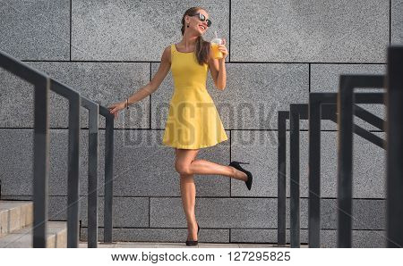 Fashion photo of young magnificent woman in sunglasses. Long-haired girl in little yellow dress posing with orange cocktail.