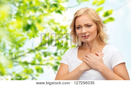 people, healthcare, heart disease and problem concept - unhappy woman suffering from heartache over green natural background