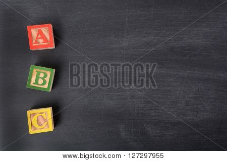 three wooden blocks on blackboard letters ABC
