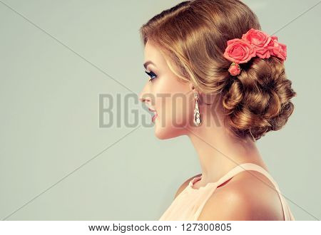 Beautiful model with elegant hairstyle . Beautiful woman with fashion wedding hairstyle and colourful makeup . Rose flower on hair  head .