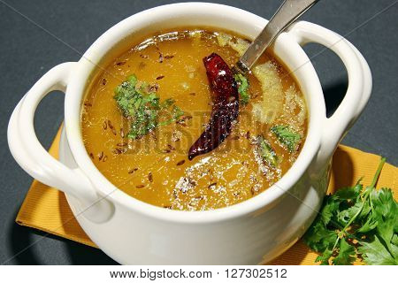 Arhar Daal soup with tempering of red chili cumin seeds and garlic with cutter on a moody background with copy space.