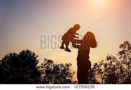 Silhouette Of Mather With Her Toddler Against The Sunset