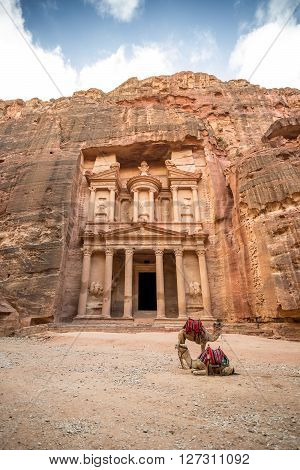 Front view of the famous Al-Khazneh (aka Treasury) with camels resting next to it in the ancient city of Petra (Jordan)