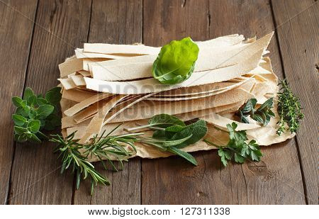 Wholegrain artisan pasta and herbs on old wooden table