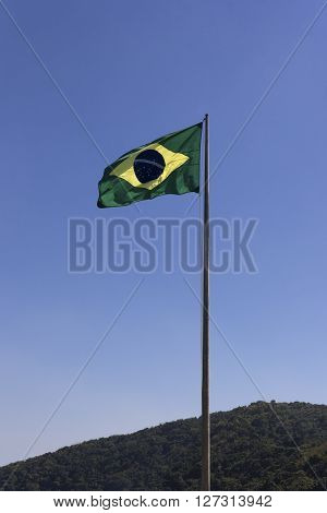 The National Flag of Brazil in blue sky background, vertical