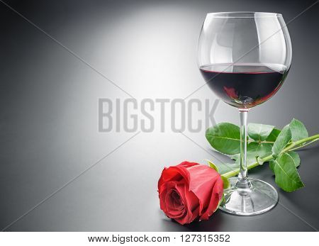 Glass of red wine and red rose flower arranged with some space on neutral gray gradient background.