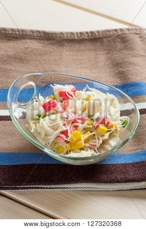 Crab sticks with rice noodles in glass bowl on textile