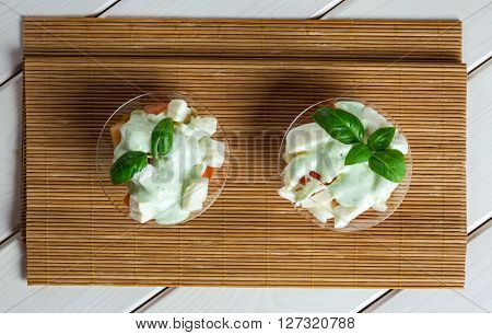 Greece style salad in green sauce in glass bowl on textile