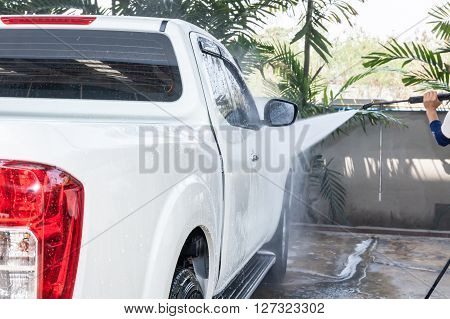 People Cleaning And Washing Car With High Pressure Washer