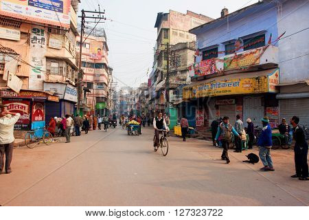 VARANASI, INDIA - JANUARY 2, 2013: People movement with the cycles on the busy indian street with the old buildings at evening on January 2, 2013.Varanasi urban agglomeration had a population of 1435113