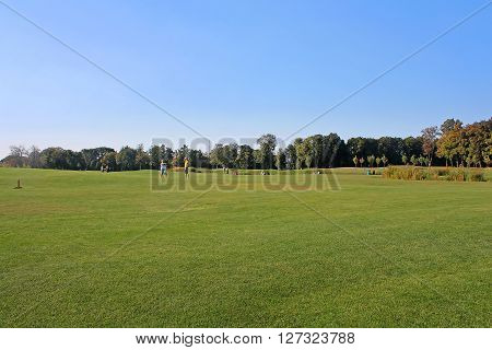 KYIV, UKRAINE - SEPTEMBER 14, 2014: Mezhyhirya - former private residence of ex-president Yanukovich now open to the public, Kyiv, region Ukraine. Unidentified people are resting on the golf field.