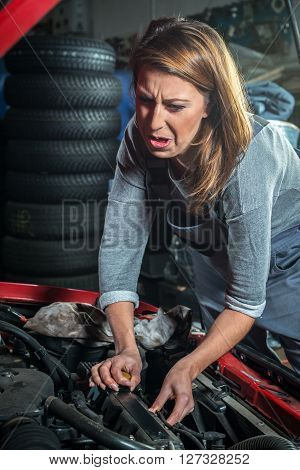 Young stressful female car mechanic in auto repair service, red automobile with tire in background