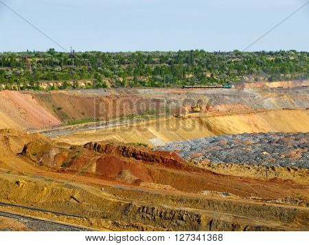 Fields of depleted iron ore with trees on the background