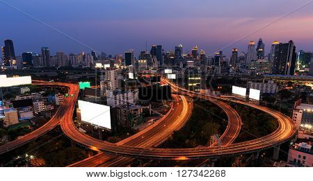 Scene of Bangkok high-rise buildings and traffic light trails on expressway at dusk
