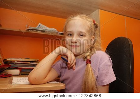 Young Schoolgirl Is Sitting Near The Desk