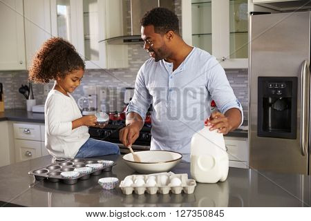 Black dad and young daughter baking together in the kitchen