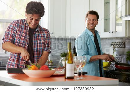 Male gay couple preparing a meal together in the kitchen