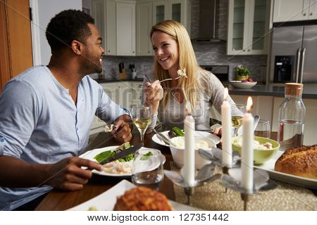 Romantic mixed race couple eating evening meal in kitchen