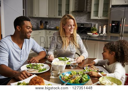 Girl and her mixed race parents dining in their kitchen