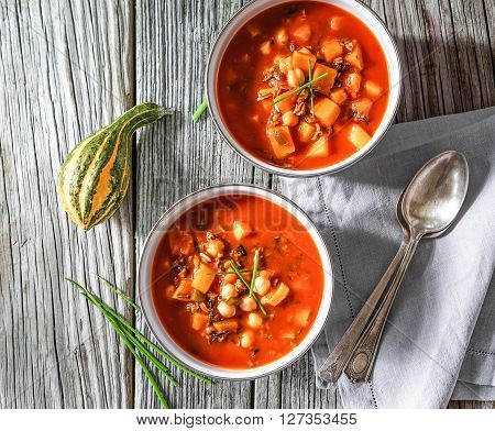 Vegetarian tasty spicy chili chick pea pumpkin wild rice soup, pozole, stew bowls on a wooden background