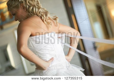 Bridesmaid Helping To Put Brides Elegant Luxury White Dress.