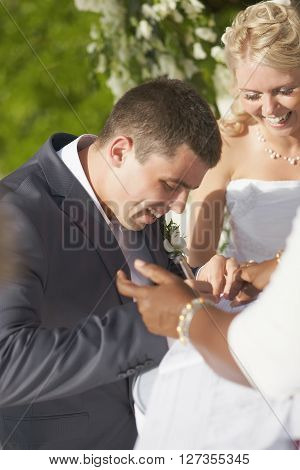Gorgerous Wedding Couple Putting Their Signatures In Marriage Certificate During Ceremony.