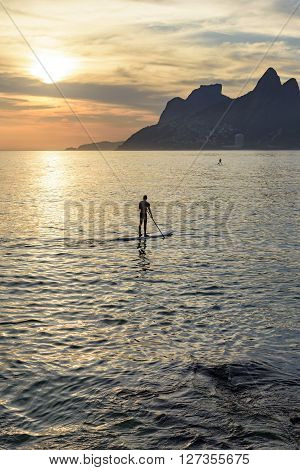 Stand up paddle at Arpoador beach in Ipanema during sunset