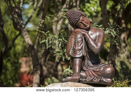 Statue of bronze buddha sleeping in a garden by mesquite tree